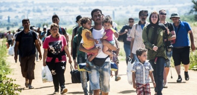 A man carries two children as he walks with other migrants near the southern Serbian village of Miratovac, travelling on foot from Macedonia to Presevo in Serbia, on August 25, 2015. At least 2,000 more migrants flooded overnight into Serbia in a desperate journey to try and go on to Hungary, the door into the European Union, a UN official said on August 24. More than 9,000 people, mostly Syrian refugees, have arrived to Serbia those last three days. AFP PHOTO / ARMEND NIMANI